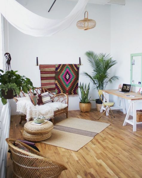 a welcoming boho space with a trestle desk, colroful rugs, potted plants, rattan and jute furniture