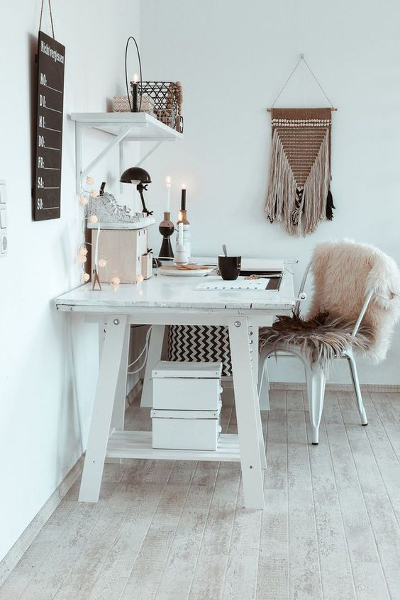 a white boho home office with a large desk, a metal chair with a pink fur cover, candles, lights and a macrame hanging