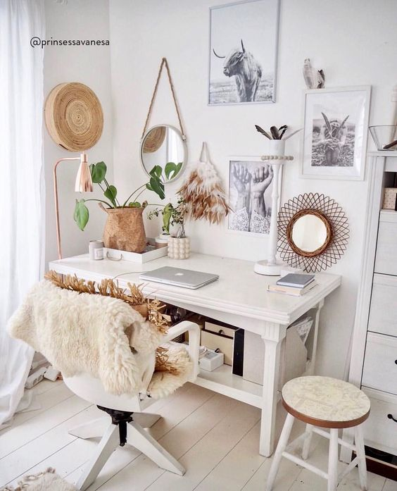 a white boho home office with a vintage desk, some chairs, faux fur and rattan, a basket, a gallery wall and some plants