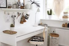 a white boho home office with open shelves, a white desk, a chair with a fringe cover, a boho ottoman, a macrame hanging and potted plants