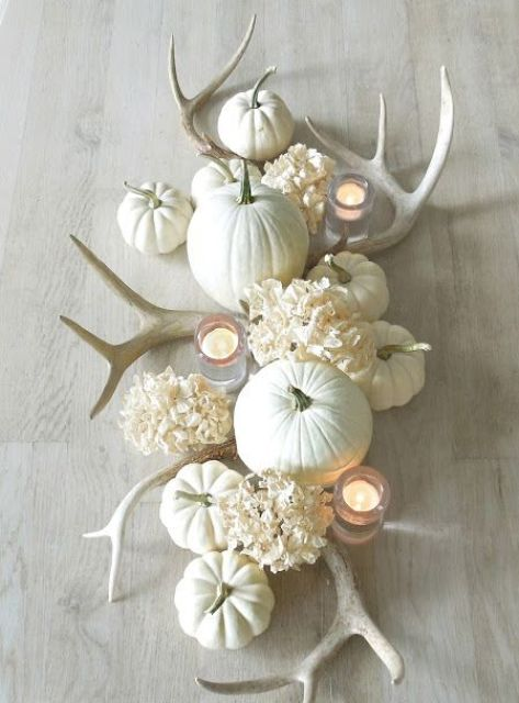 a white fall centerpiece of pumpkins, hydrangeas, antlers and candles is very pretty and elegant