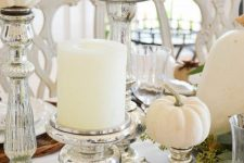 a white fall centerpiece of white pillar candles and white pumpkins in mercury glass stands
