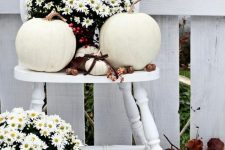 a white vintage chair with white potted blooms, white pumpkins and nuts and acorns feels very natural