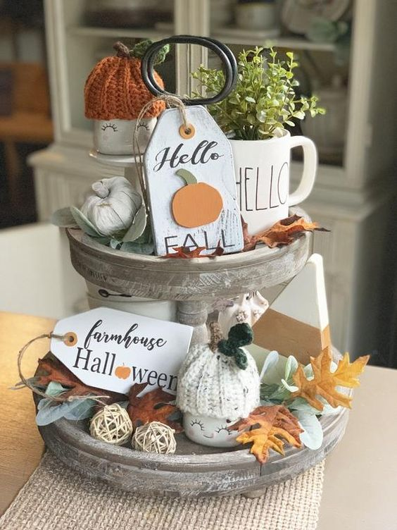 a whitewashed wooden stand with faux pumpkins, fall leaves, greenery in a mug, tags, knit pumpkin caps