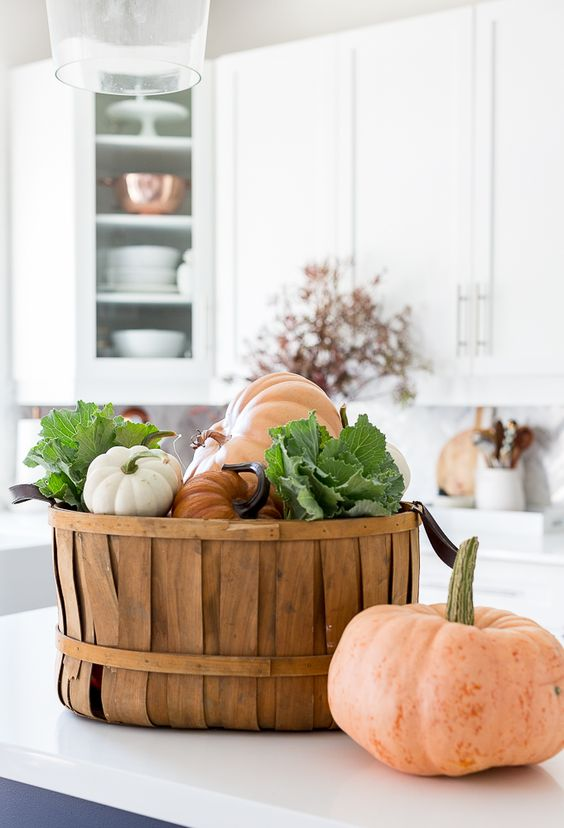 a wooden basket with fresh pumpkins and veggies is a cool and edible fall decoration