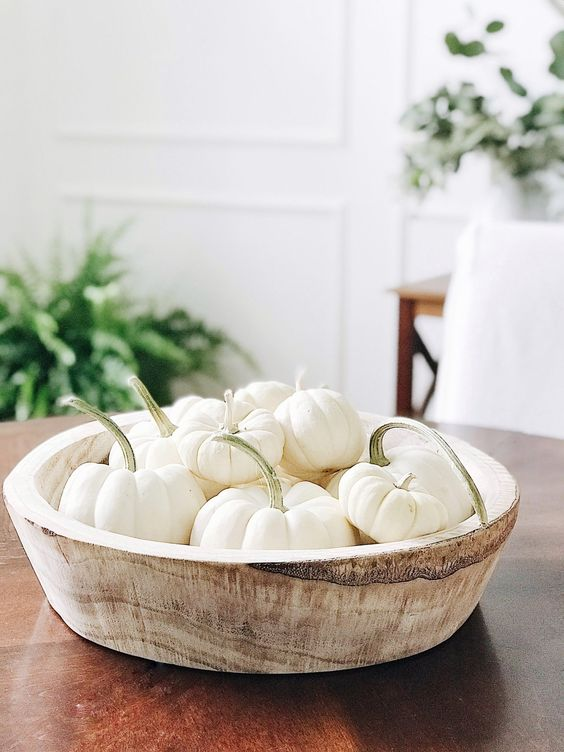 a wooden bowl with white pumpkins is a cool decoration or a centerpiece that you can make very fast