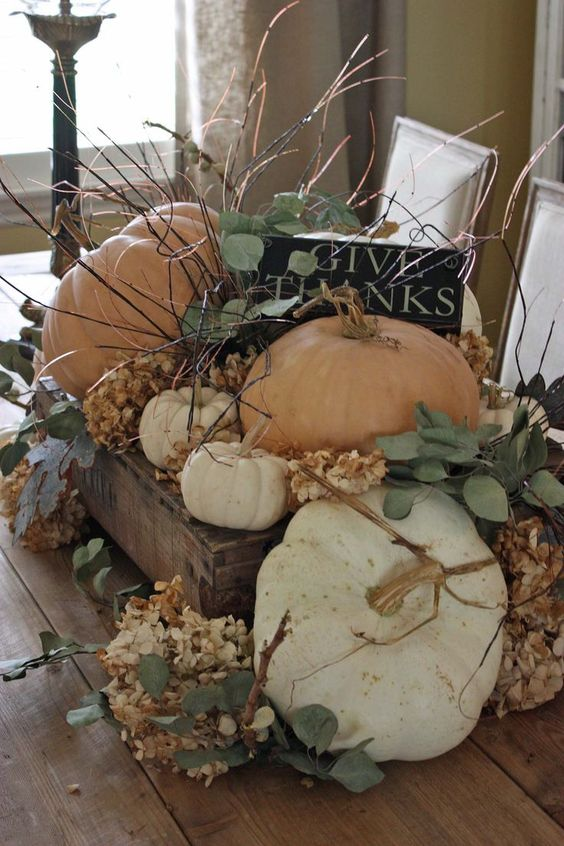 a wooden crate with dried hydrangeas, greenery, pumpkins, a black sign and los of twigs for a rough fall centerpiece