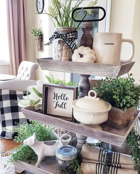 a wooden fall stand with potted greenery, white pumpkins, signs, jars and mugs plus plaid and striped textiles
