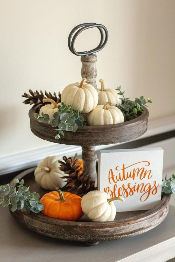 a wooden stand with eucalyptus, white and orange pumpkins and pinecones and a small sign