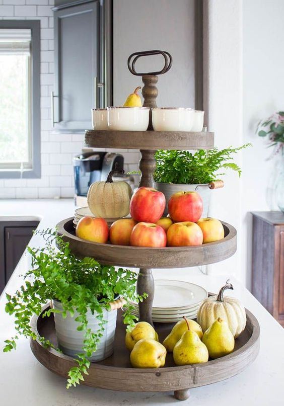 a wooden stand with potted greenery, fresh apples and pears plus pumpkins and plates
