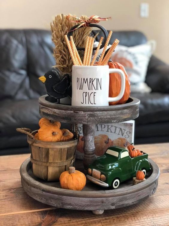 a wooden stand with wheat, fake pumpkins, a pretty mug and some colorful figurines