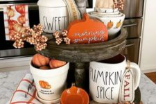 a wooden stand with white and orange porcelain, berries, fake pumpkins and plaid napkins for the fall