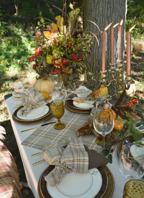 a woodland fall tablescape with plaid textiles, fall blooms and foliage, copper candles and printed plates