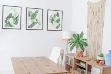 an airy boho chic home office with a wooden desk and a storage unit, potted plants, a macrame hanging, a bright rug and a gallery wall