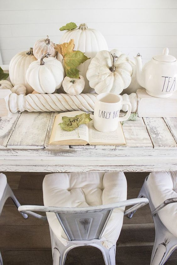 an airy fall centerpiece of white and neutral pumpkins, fall leaves and railing for a neutral vintage look