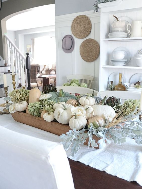 an all-natural fall centerpiece of a dough bowl, neutral pumpkins, green hydrangeas and pale greenery and wheat