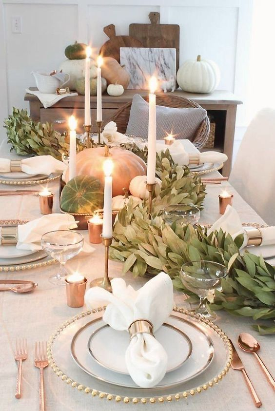 an all-natural fall centerpiece of pumpkins and gourds, a leafy garland and thin and usual candles