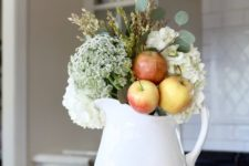 an arrangement of a white jug, white blooms, greenery, apples and a copper mug for simple and chic fall decor