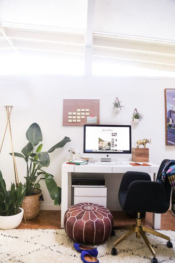 an attic boho chic home office with a white desk, a leather ottoman, a black chair, potted plants on the floor and some on the walls