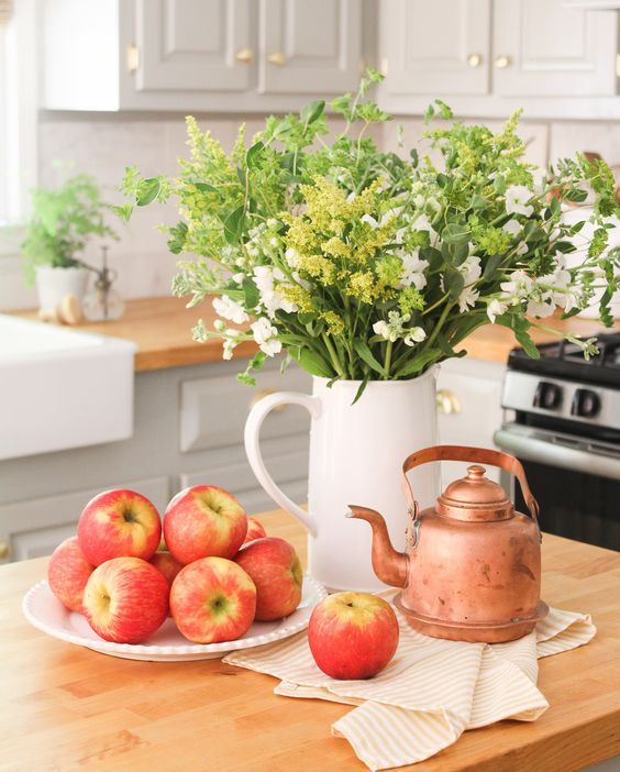 an early fall decoration - a jug with greenery and white blooms, fresh apples and a copper kettle