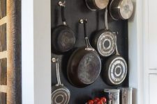 an open storage unit with open shelves and a chalkboard with hooks attached, which are ideal for hanging pots and pans