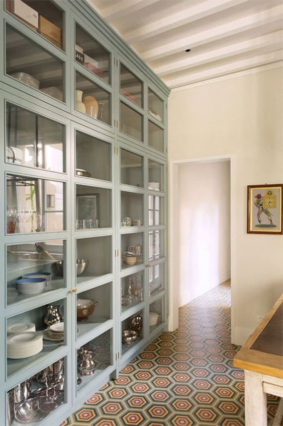 an oversized glass fronted cabinet with many compartments is great for storing your tableware and other stuff