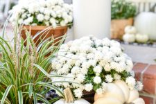 beautiful fall decor with white potted blooms, grasses, pumpkins, acorns and leaves is fantastic