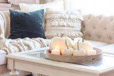 cozy neutral fall decor – a tray with white pumpkins and pillar candles, a white blanket in a basket