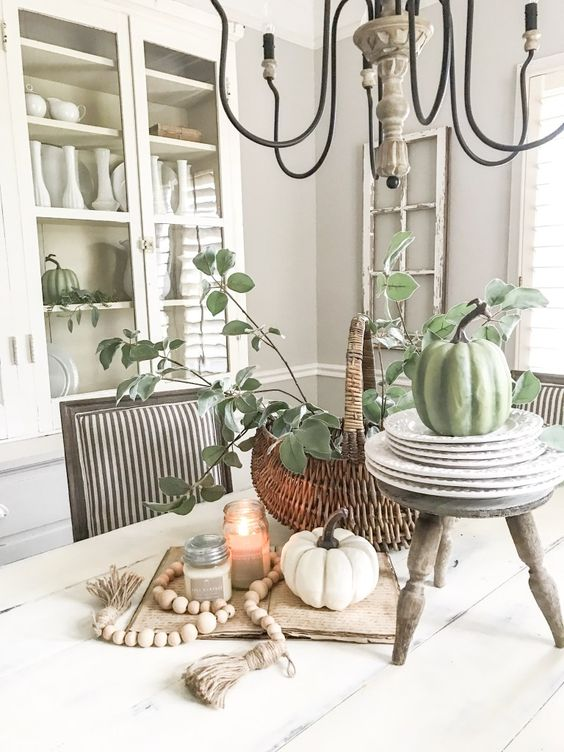 fall kitchen decor with white and green pumpkins, candles, wooden beads and a basket with greenery