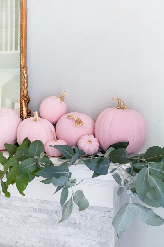 light pink pumpkins with gilded stems and lots of greenery will make the mantel look super glam and fall-like