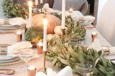 natural pumpkins and a greenery garland plus candles decorate a fall tablescape in a very chic way