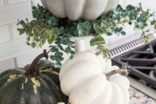 natural pumpkins including one on a stand with eucalyptus are neutral and cozy fall decor