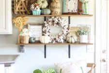 neutral fall pumpkin, a cotton wreath, blooms in vases, potted greenery and a wheat arrangement for a fall kitchen