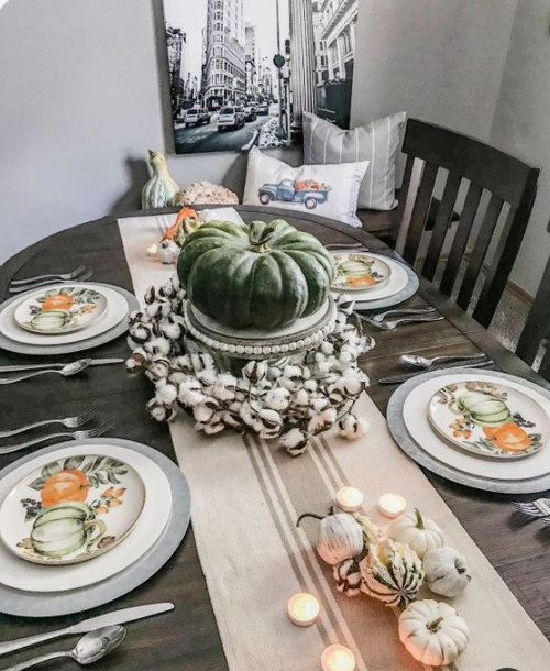 printed plates, a striped runner, candles, neutral pumpkins and cotton and a large heirloom one as a centerpiece