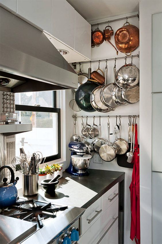 railings built into an awkward nook are great for hanging all the pans, teapots and pots without taking shelf space