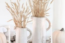 rustic white fall decor with a neutral table runner, white pumpkins, white jugs with wheat and candles