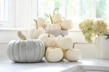 simply stack white pumpkins on the table to create relaxed and chic fall decor with a natural feel
