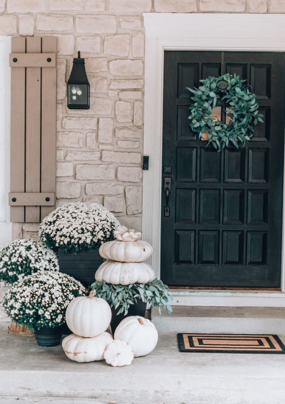 white outdoor fall decor with white potted flowers and white stacked pumpkins and greenery is very chic