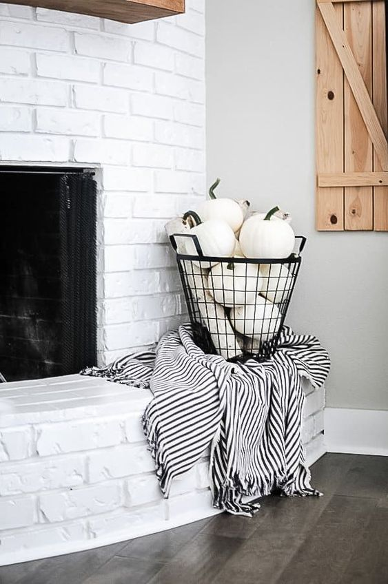 white pumpkins in a black wire basket and a a striped blanket for styling your space for the fall