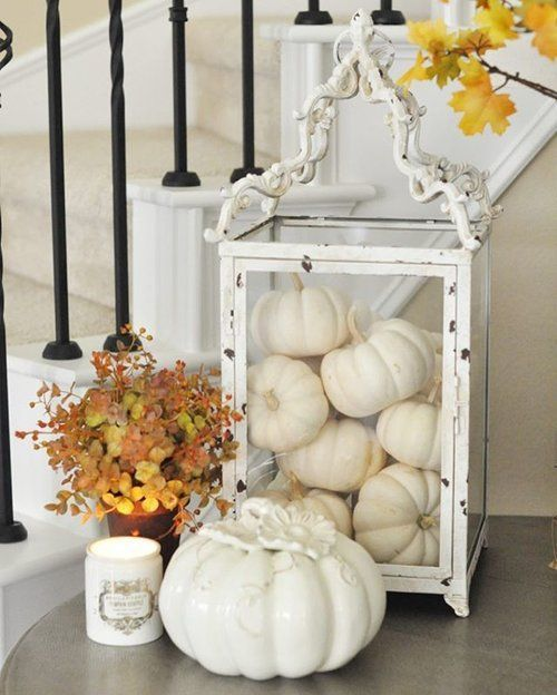 white pumpkins in an oversized white glass candle lanterns, a porcelain pumpkin and candles for fall decor