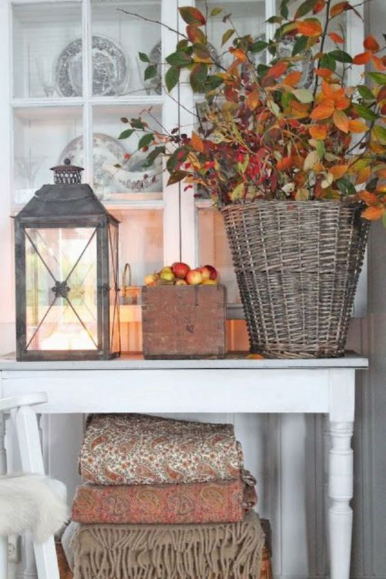 a basket with branches with berries and leaves, apples in a box and a candle lantern for a cozy touch