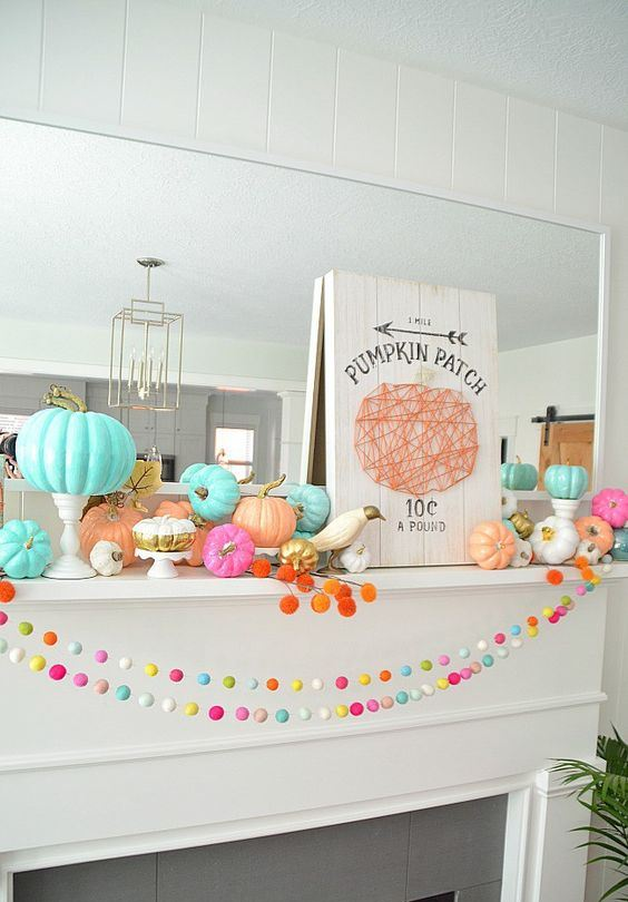 a beautiful colorful mantel with bright garlands, bold pumpkins, faux birds and a cool yarn sign