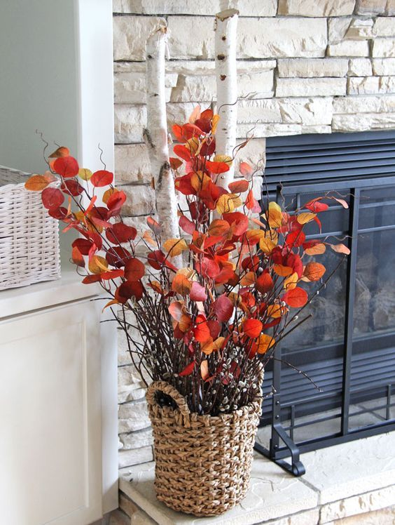 a bold fall decoration of a basket with thick birch branches and branches with bright leaves