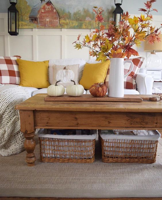 a bold fall leaf arrangement in a jug and some natural pumpkins for a rustic fall coffee table