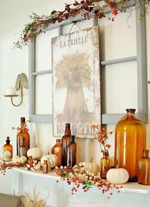a bright fall mantel with a vintage sign, faux berries and branches, white pumpkins and amber-colored bottles