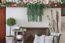 a bright fall mantel with cascadign greenery, pastel pumpkins, greenery, branches in a bucket and a wooden basket