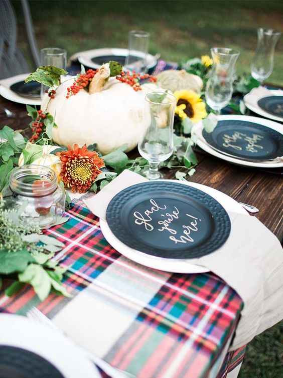 a bright fall table setting with plaid fabric, blakc plates, blooms, greenery and pumpkins looks very cute