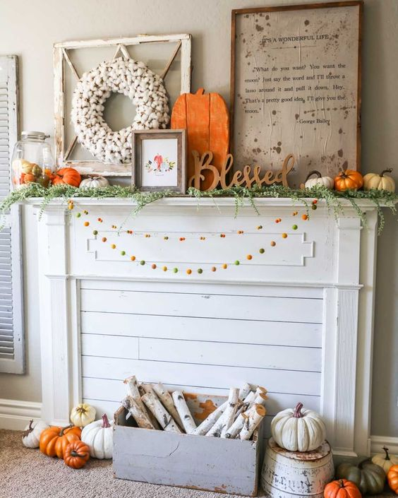 a bright rustic flal mantel with colorful pompom garlands, a crate with birch branches, lots of pumpkins, signs and a cotton wreath