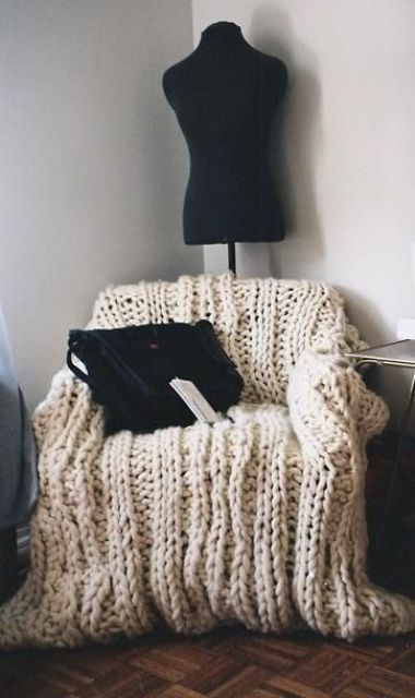 a chair covered with neutral chunky knit is a gorgeous piece to sit on and its imperfect look is very chic