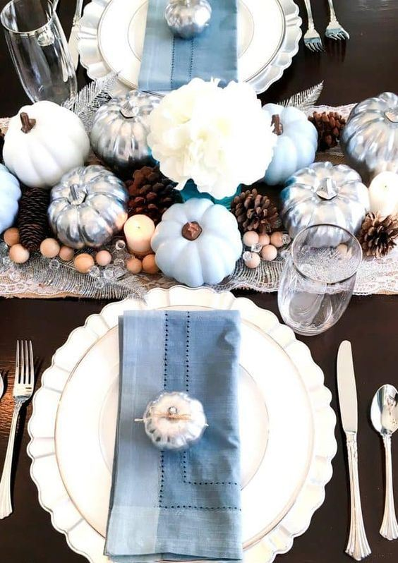 a chic fall tablescape with light blue pumpkins, blue napkins, silver touches, pinecones and wooden beads